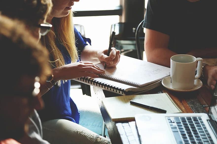 pessoas reunidas em frente a cadernos e computador (o maior ativo de uma empresa: pessoas)