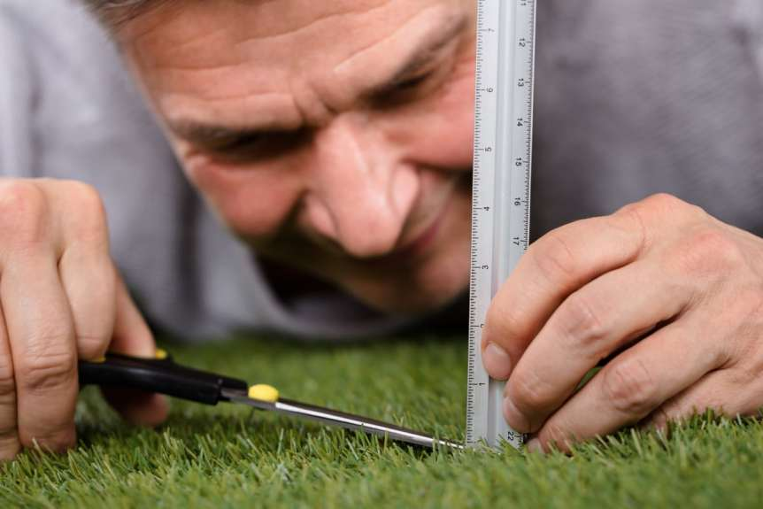 Man trying to cut grass perfectly