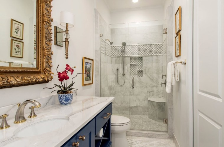 White, tiled, bathroom with gold finishes