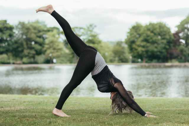 unrecognizable woman showing three legged downward facing dog pose