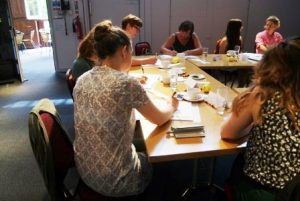 Image shows a scene from a workshop with participants sitting around a table
