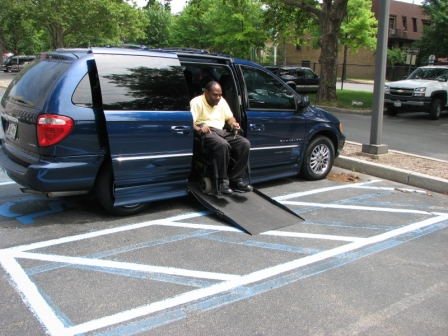 Photo of disabled person exiting his van using a wheelchair ramp in accessible aisle