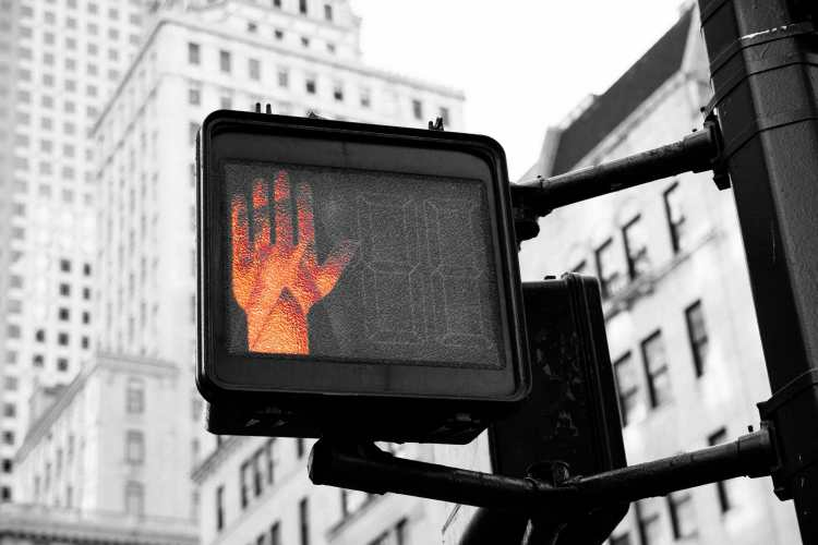 Picture of a crosswalk stop signal to remind us to stop and thing to avoid doing these five things while launching your career with ADHD.