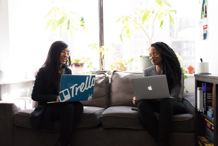Two girls sit next to each other while using their laptops. They are feeling less stress at work after working with a career coach in Houston, TX with Accessible Career.