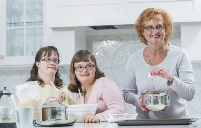 Mother and two daughters with down syndrome, baking