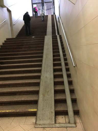 An extremely steep wheelchair ramp up a flight of stairs.