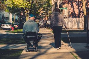 Individual in a wheelchair and individual with a cane walking down a sidewalk
