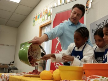 Chef and food literacy advocate Jamie Oliver helping Pacific Elementary students with a cooking demonstration.