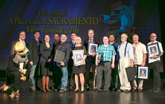On stage at the Crest Theatre (from Left) Festival Mascot Quentin Sacramento, Festival Director Gary Martin and filmmakers Jeffrey Dym, Jodie Fleming, Larry Menard, J. Thomas Schuessler, Nick Coleman, Danna Wilberg, John Maniachi, Eric Sanderson, Access Sacramento Board Chair Robin Scott Peters, and writers Scott Slotterbeck, Chris Henry and Darrel Scheidegger (All photos by Tia Gemmell, Riverview Media Photography)