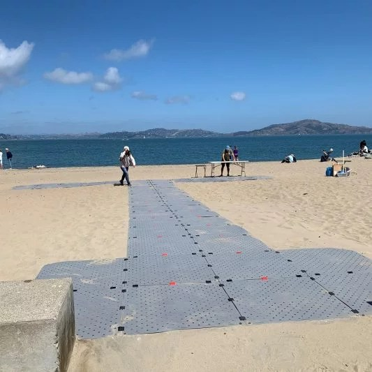"""The grey Beach Trax pathway is set up in a """"T"""" layout over sand at the bay."""