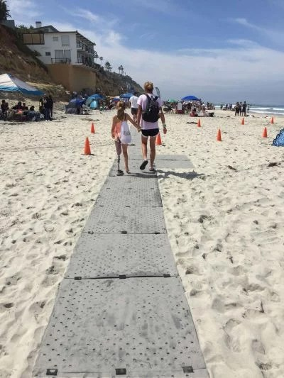 Images shows a woman and young lady walking side-by-side holding hands down a grey Access Trax pathway on sand at the beach. The young lady has a prosthetic leg.