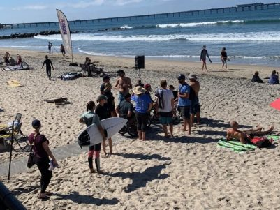 Surfers and family gather at the end of the pathway to hang out and watch the competition.