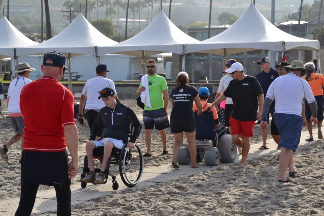 People walk and use wheelchairs over a grey Beach Trax pathway on sand at the event.