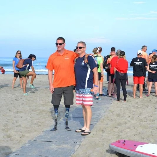 A man with 2 prosthetic legs and a man wearing American flag themed shorts pose for a photo standing on the Beach Trax pathway at the beach.