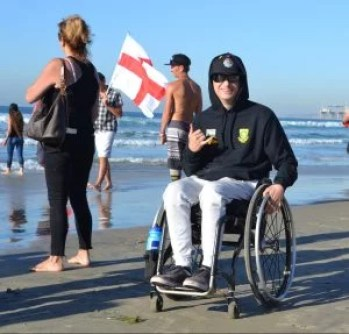 Adaptive surfer Albert poses for a picture using his wheelchair on the sand at the beach.