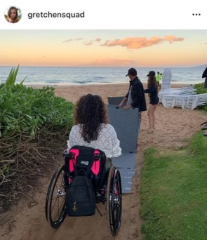 A woman with long curly brown hair using a wheelchair is in the foreground with a man and woman unfolding a grey Beach Trax pathway on the sand at the beach during sunset in the background.