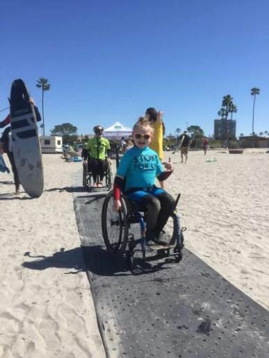 A blonde girl moves her wheelchair atop Beach Trax at the beach.