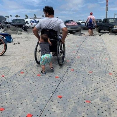 A man in a wheelchair uses Beach Trax to traverse beach sand.