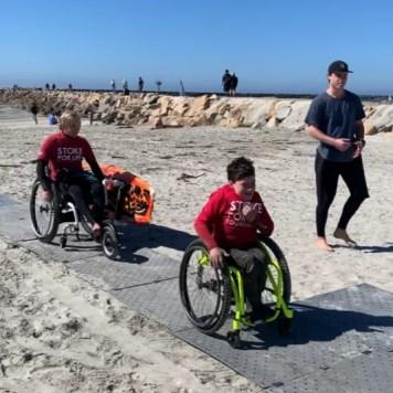 A young boy in a wheelchair atop Beach Trax.
