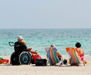 A beach scene with turquoise water and a man seated in a wheelchair sitting next to two women in beach chairs.