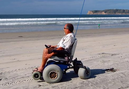 A man uses a power beach chair with large wheels on sand at the beach.