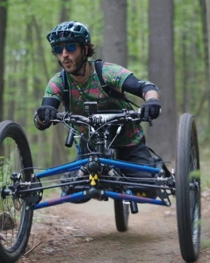 Greg flies down the forest trail on his handcycle.