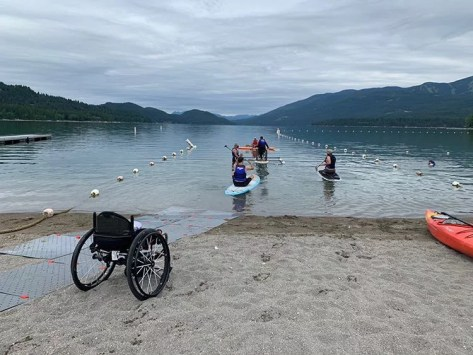 Image shows adaptive athletes paddling on a lake in Montana on a cloudy day. In the foreground is the sandy lake shore with grey Access Trax mats leading to the water. There is an empty manual wheelchair.