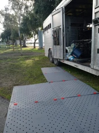 Image shows a horse trailer on the right parked on grass with trees in the background. The trailer is open and on the ground is a platform of interconnected grey square Access Trax mats for wheelchair access.