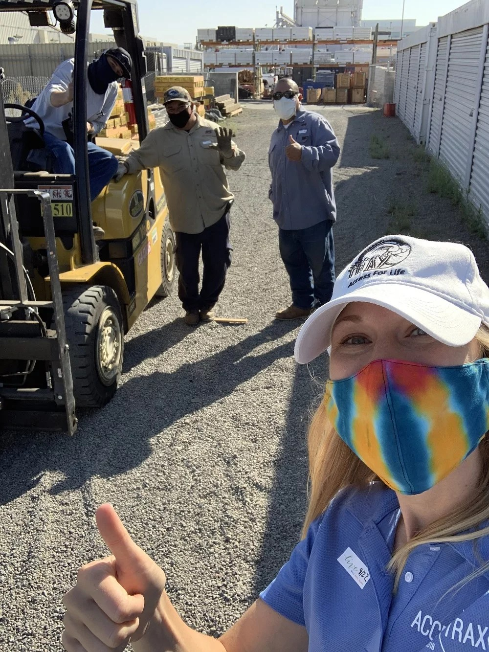 Image shows Kelly taking a selfie with 3 men who work for a local gas and electric company. They are standing by and in a forklift on loose gravel. They are all wearing face masks. Kelly is giving the thumbs up!