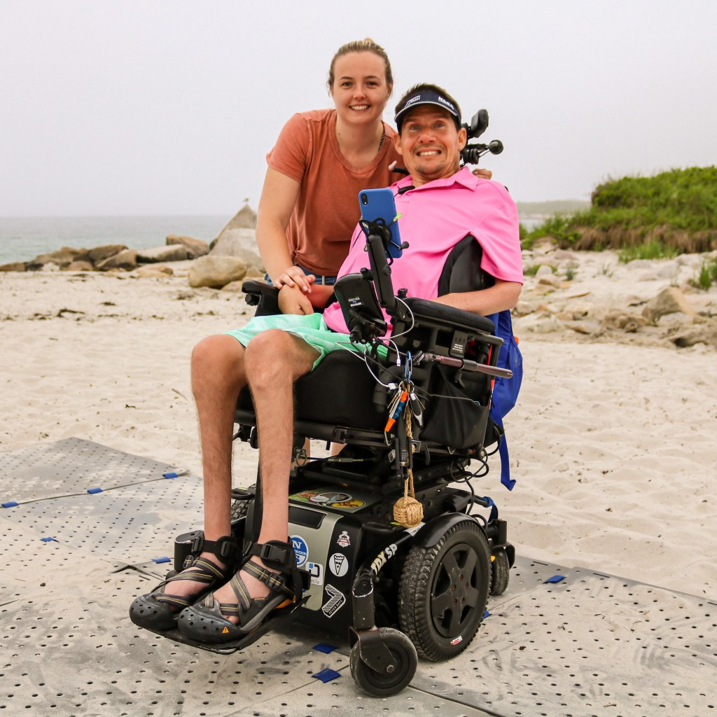 A woman in a tshirt and shorts smiles next to a man in a pink collared shirt and shorts at the beach. The man is in his power wheelchair which is on a grey Access Trax pathway on sand.