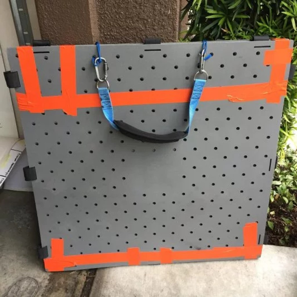 A stack of grey square Access Trax mats lean against a wall. They are connected to the shoulder carrying strap at the top and have orange duct tape across the top, bottom, and corners.