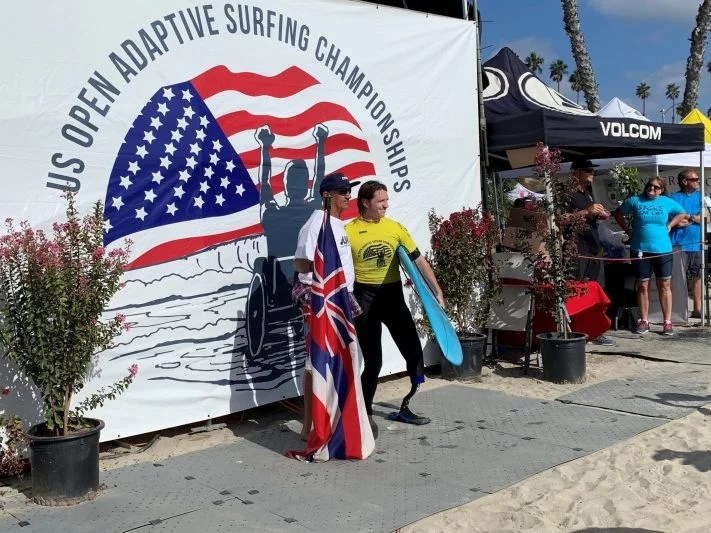2 men pose for a photo at an adaptive surf event in front of a large banner at the beach. One man holds the Hawaii state flag and the other is an adaptive surfer holding his blue surf board. He has a prosthetic leg. They are standing on the Access Trax pathway.