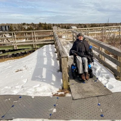A man wearing winter clothing smiles seated in his power wheelchair on a snow covered wooden bridge. His is on grey Access Trax portable mats.