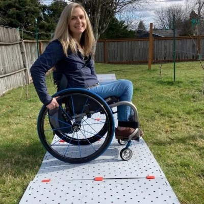 A blonde woman wearing jeans and a blue zip up jacket smiles in her grassy backyard. She is seated in her manual wheelchair which is on a grey Access Trax portable pathway.