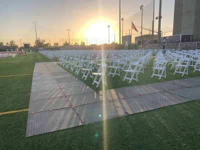 Image shows white foldup chairs arranged in perfect rows on a turf football field during sunset. There is a 6ft wide Access Trax portable wheelchair access pathway around the chairs.