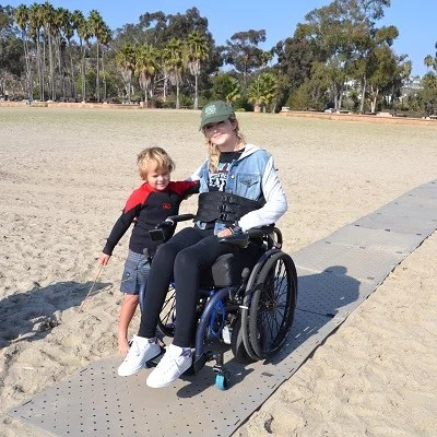 Image shows a blonde woman wearing a jean jacket and black pants with a baseball hat seated in her manual wheelchair smiling with her young son by her side. They are on a grey portable pathway over sand at the beach.