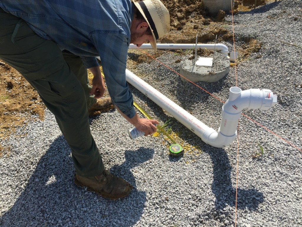 Prepping drain lines on our cordwood home. Here we're setting four feet intervals to measure slope