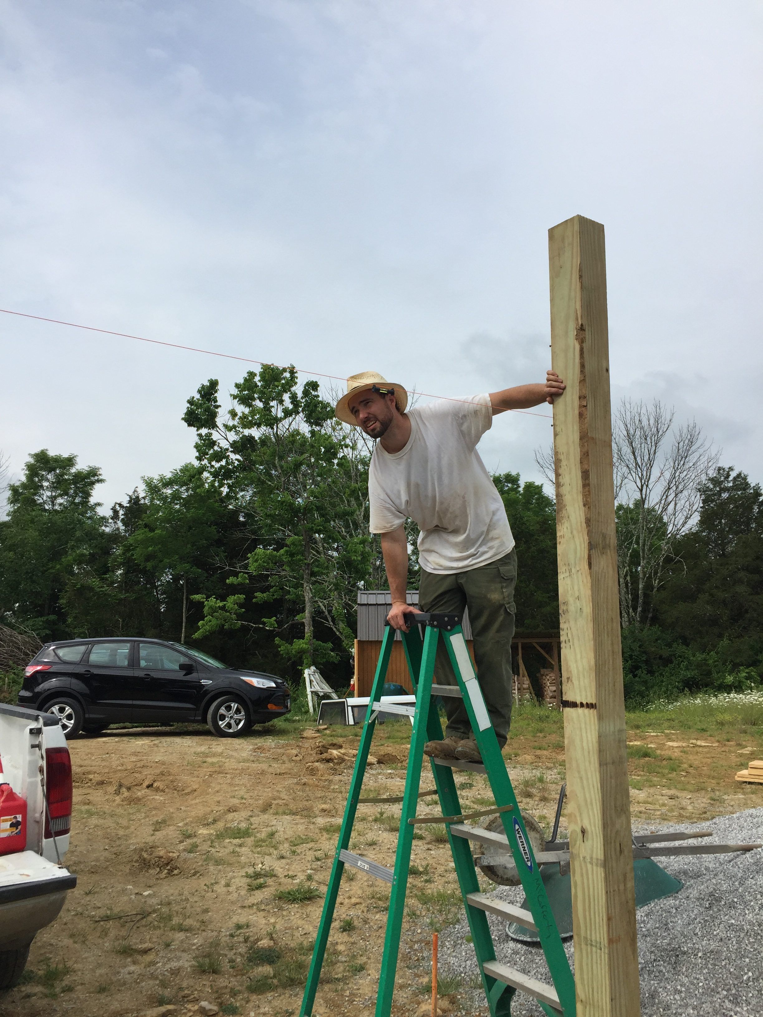 Checking to make sure notches are level in our DIY pole frame for a cordwood house