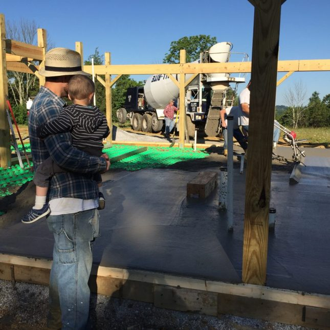 Watching the concrete slab be poured for our off-grid cordwood house