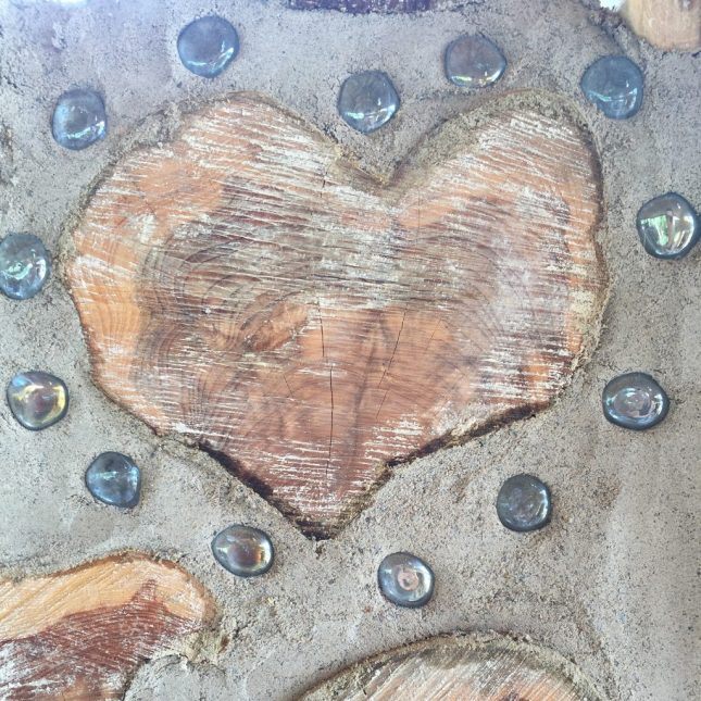 You can add fun designs into your cordwood wall. Here, a heart-shaped log has been adorned with glass pebbles like you would use in centerpieces or other decor!