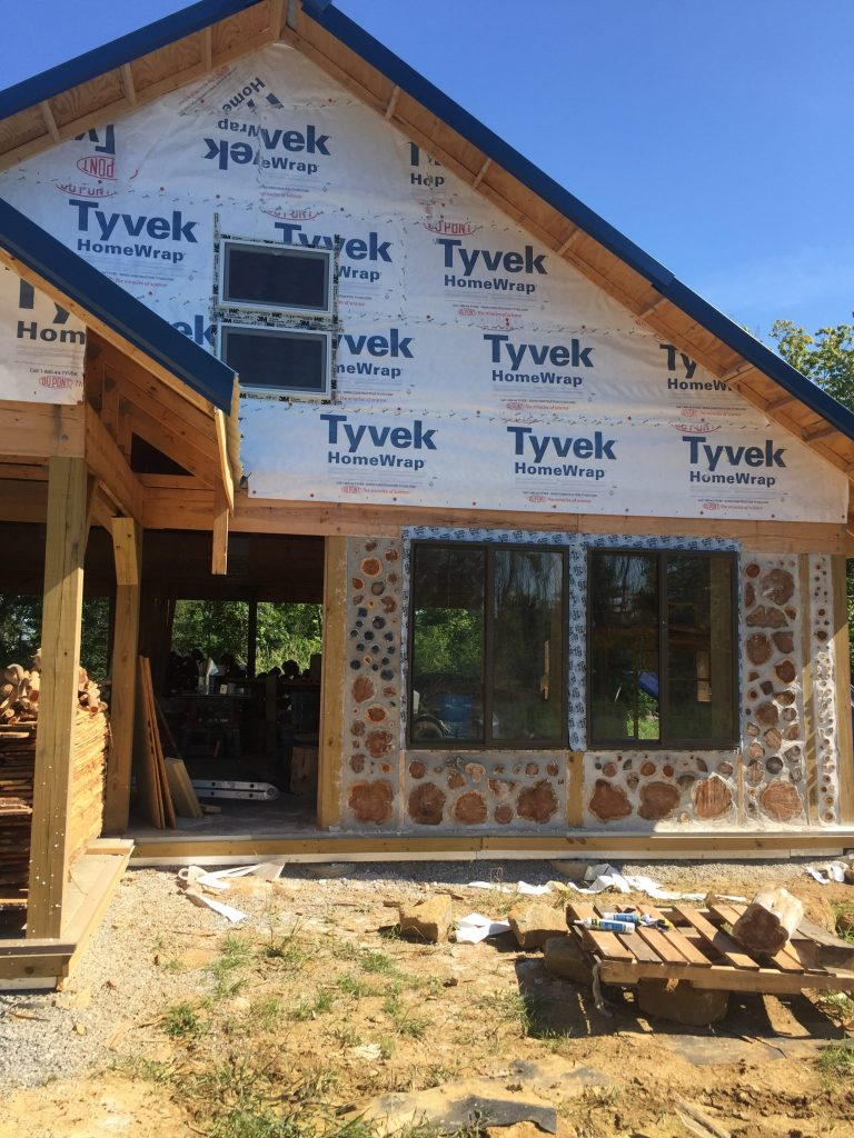Front of a cordwood house in progress - from Accidental Hippies