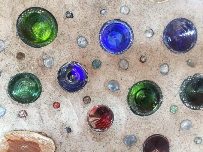 Colored glass bottles in a cordwood wall let in beautiful light!
