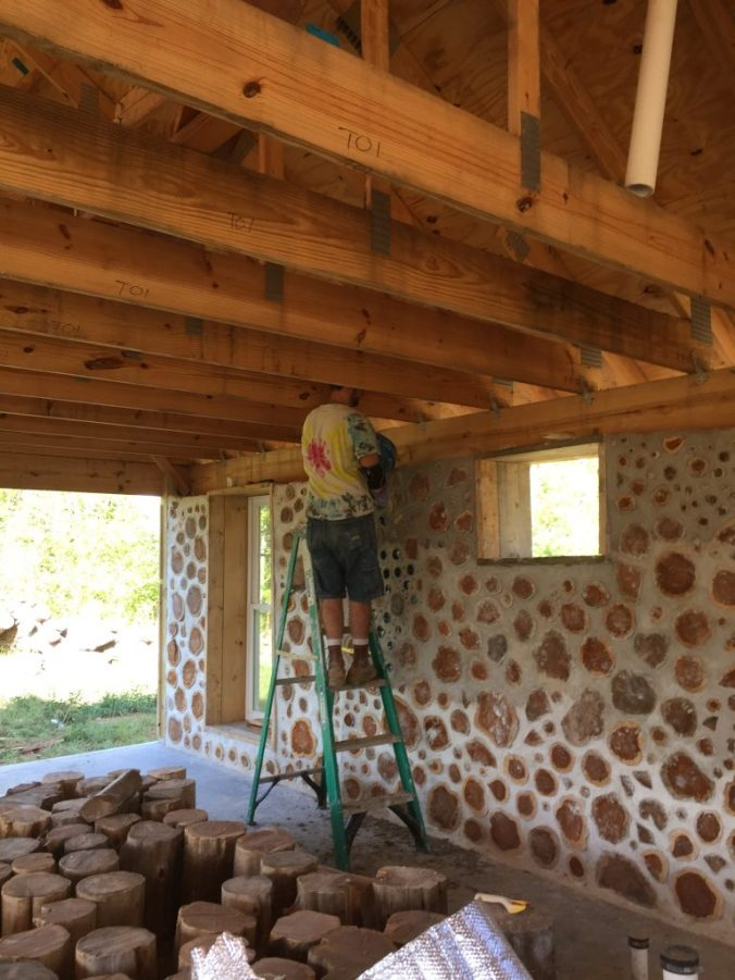 Mark pours a mix of sawdust and masonry lime into the middle of a cordwood wall. The sawdust acts as insulation and the lime keeps it rot and pest resistant.