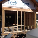 2x6 stud framed wall with window openings set between 6x6 posts in a pole frame house