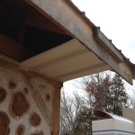 Soffit installation in progress on a cordwood house