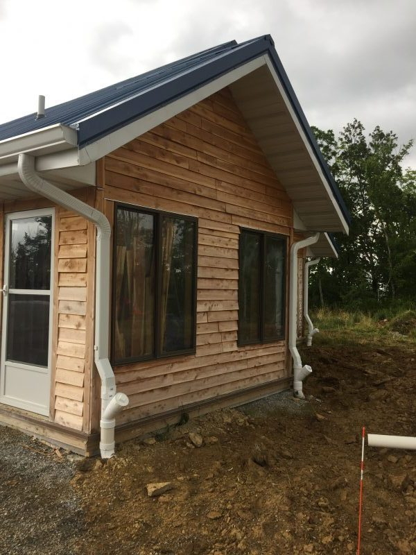Gutters feed rainwater from our metal roof into our cistern to supply our off-grid house. Learn more!