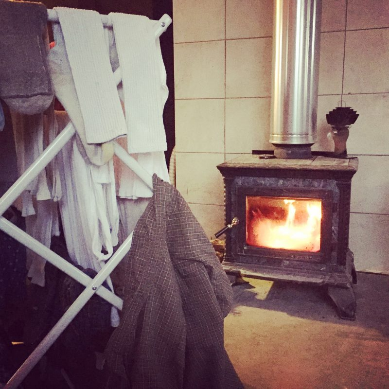 Air drying our clothes by the woodstove is just one way we save power off grid in the winter. What else do we do living with off grid solar?