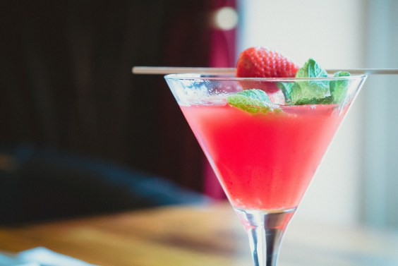 Memorable Family Holiday pink/red cocktail with a strawberry and mint in it