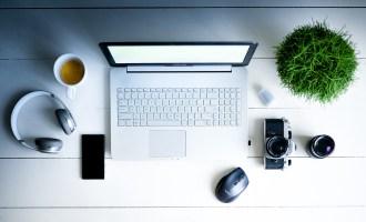 Blogging flat lay showing computer, camera, camera lens, headphones, coffee, plant