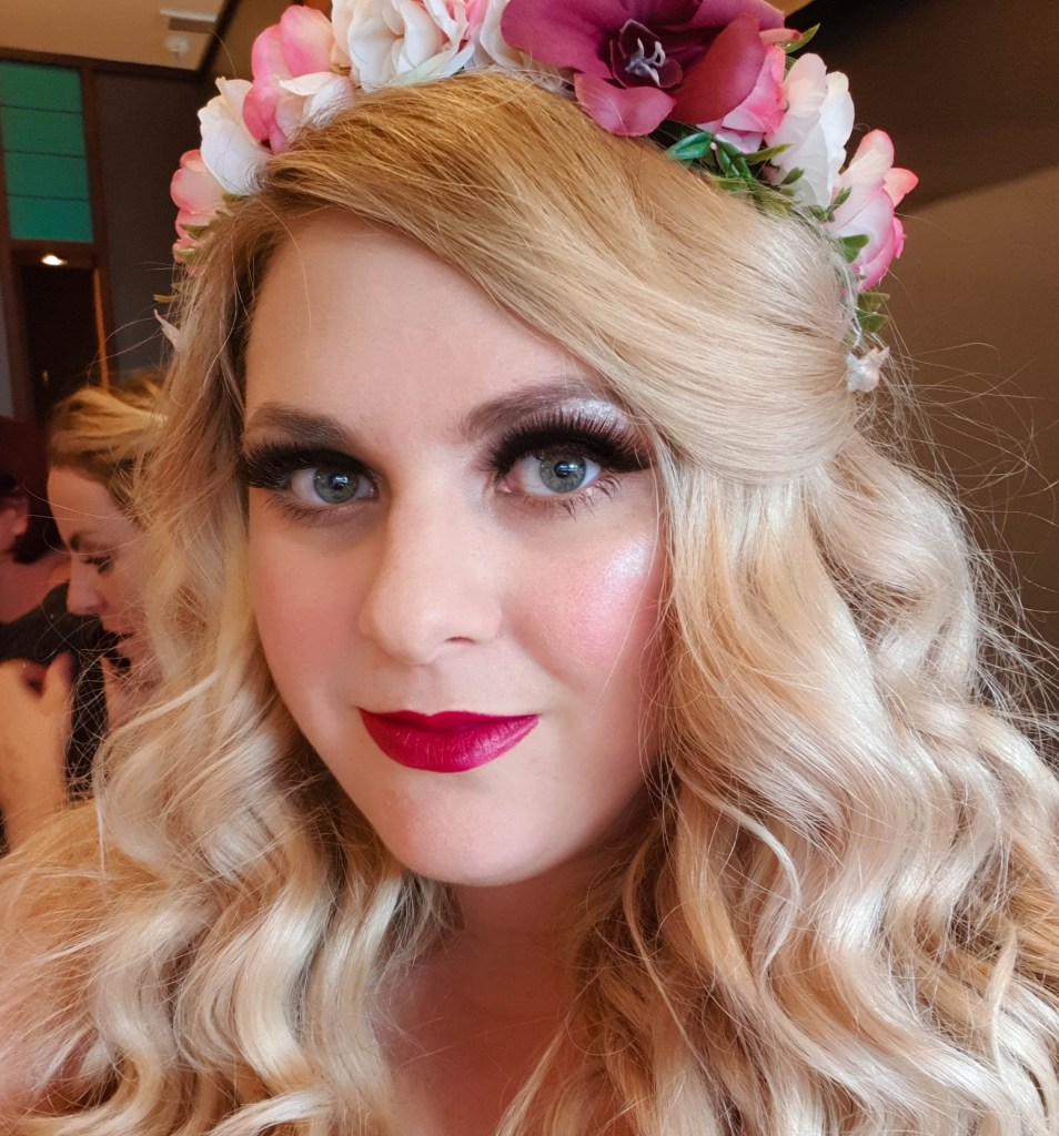 Please vote for me in the Bibs 2018, this is a close up of my face, I have blonde curly hair and a flower crown